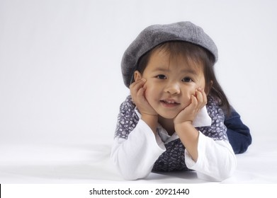 happy little asian girl wearing a hat photographed in a studio against white background