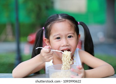 Happy little Asian kid girl eating Instant noodles at the garden with copy space.
