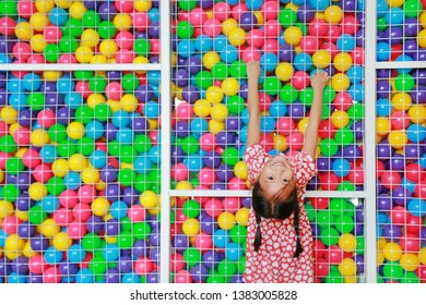 Happy little Asian kid girl playing climb and hanging on cage of playground colorful toy ball with looking camera.