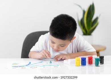 Happy little Asian kid at the table draw with water color Learning and education of kid.