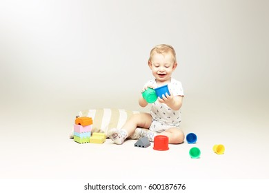 Happy little baby boy playing with some toys.