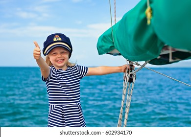 Happy little baby captain on board of sailing yacht watching offshore sea on summer cruise. Travel adventure, yachting with child on family vacation. Kid clothing in sailor style, nautical fashion.