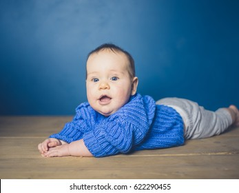 A happy little baby is exploring and learning to crawl