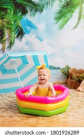 Happy little baby girl bathes in bright inflatable pool on a sandy beach with palm trees by the sea