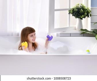 Happy little baby girl sitting in bath tub playing with duck toys in the bathroom. Portrait of baby bathing in a bath full of foam near window