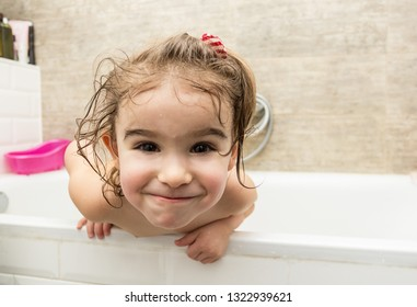 Happy little baby girl sitting in the bathroom. Smiling kid in bathroom on brown background. Infant washing and bathing. Hygiene and health care.