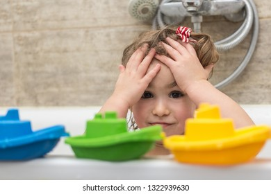 Happy little baby girl sitting in bath tub playing with colorful boats toys in the bathroom. Smiling kid in bathroom on brown background. Infant washing and bathing. Hygiene and health care.