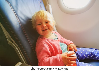 happy little baby girl travel by plane