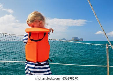 Happy little baby in life jacket on board of sailing boat watching offshore sea and tropical islands on summer cruise. Children travel adventure on family vacation. Safety during yachting with kids.