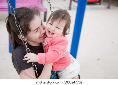 happy little baby with mom riding on a swing
