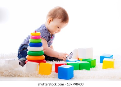 happy little baby playing with colorful cubes. development of the child. age of 7 months. isolated