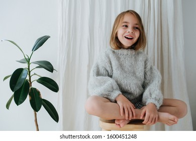 Happy little barefoot girl in a grey knitted sweater sitting cross-legged on a stool at home, in front of a curtain next to a potted plant.