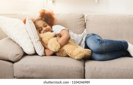 Happy little black girl sleeping with toy on sofa at home. Smiling dreamy child taking a nap on couch, copy space