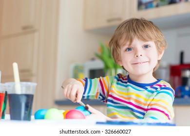 Happy little blond kid boy coloring eggs for Easter holiday in domestic kitchen, indoors. Child having fun and celebrating feast.