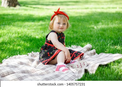 Happy little blonde girl-child in cherry pattern dress play in summer park under the trees shade of a beautiful green grass. Childhood. Concept of a happy family. Universal Children's Day
