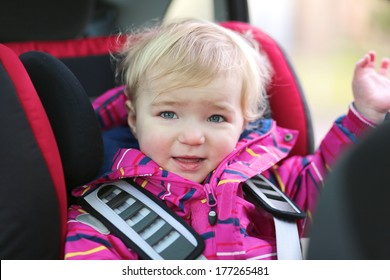 Happy little blonde toddler girl waving with her hand sitting in the car seat locked with safety belts