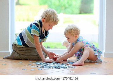 Happy little blonde toddler girl playing puzzles with her teenager brother sitting on the tiles floor next to a big street view window