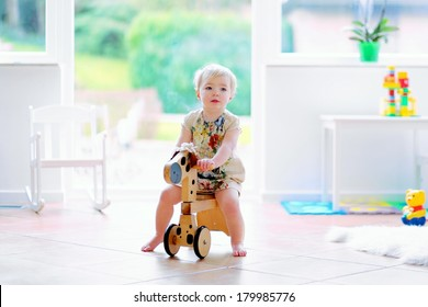 Happy little blonde toddler girl riding on wooden horse indoors in a beautiful room with big window and tiles floor