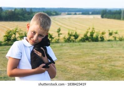 Happy little boy 5 year old walks in village with black kitty.