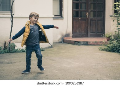 Happy little boy with arms outstretched spinning around and having fun outdoors.