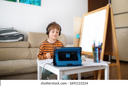 Happy little boy attending online classes from home. Child using digital tablet and headsets for connecting with teacher and schoolmates. School education and social distance during quarantine