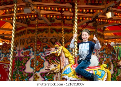 A happy little boy with Autism, Aspergers Syndrome, ADHD enjoys a ride on a merry go round in Stoke on Trent, Staffordshire
