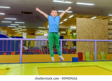 Happy little boy bouncing on an indoor trampoline at a funfair or playground with his aims outstretched