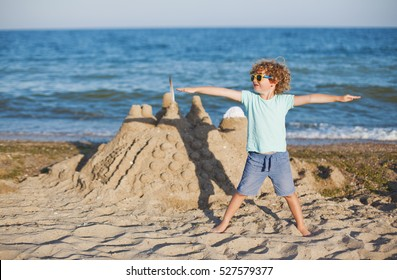 happy little boy with built sandcastle on tropical beach, child on the background of sand castle summer sea