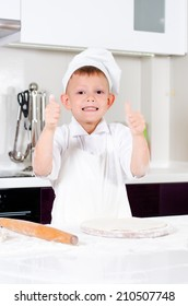 Happy little boy in a chefs uniform and hat making homemade pizza giving a thumbs up gesture of success as he stands over the pizza base on a wooden board