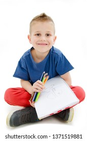 Happy little boy with colored pencils and sketch book sitting on floor. Isolated on white background