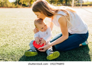 Happy little boy congratulates smiling mother and gives her a red heart gift while sitting on the lawn in the park, Mother's Day