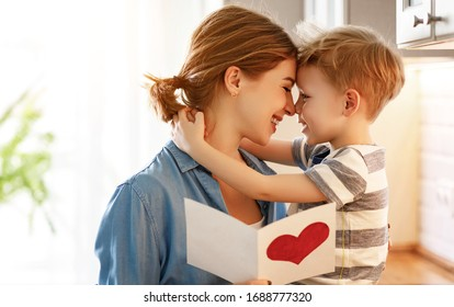 Happy little boy congratulating smiling mother and giving card with red heart during holiday celebration at home