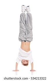 Happy little boy dancing isolated on white background. Young handsome fresh child breakdancing. Dancer kid performing extreme break dance movements.