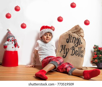 Happy little boy dressed by  father Christmas  with a red hat