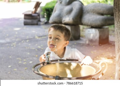 Happy little boy drinking water from fountain in the city park on a summer sunny day. Close up. Beautiful summer background with copy space