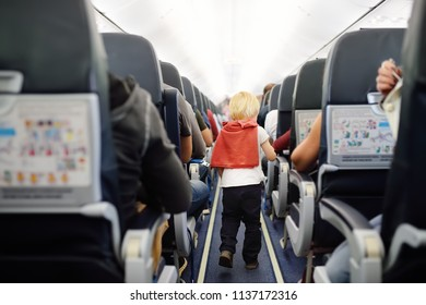 Happy little boy during traveling by an airplane. Traveling with kids. Family enjoying trip in aircraft. Transportation safety