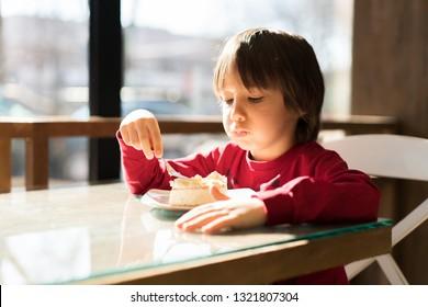 Happy little boy eating