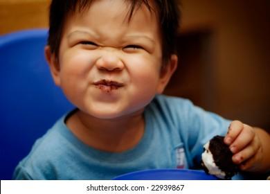 Happy little boy eating an ice cream sandwich
