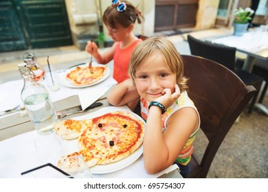 Happy little boy eating kid's pizza in the restaurant. Menu for children, animal shaped italian pizza for youngsters