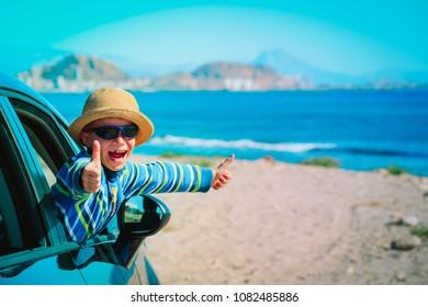 happy little boy enjoy travel by car at beach