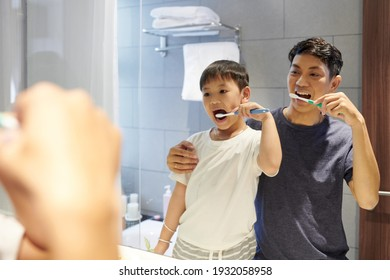 Happy little boy enjoying brushing teeth with his father in front of bathroom mirror before going to bed