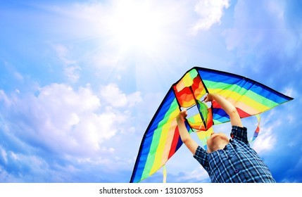 Happy little boy flies a kite in the sunny sky