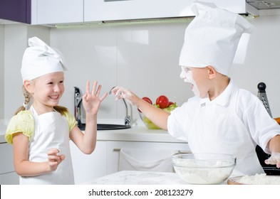 Happy little boy and girl baking in the kitchen in their cute white chefs uniforms laughing and fooling around with flour on their faces