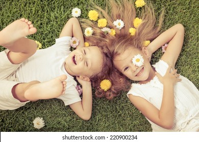 Happy little boy and girl lying on the grass at the day time. Concept of a brother and sister forever.
