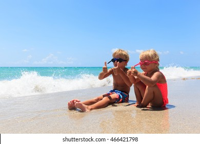 happy little boy and girl play with water on beach