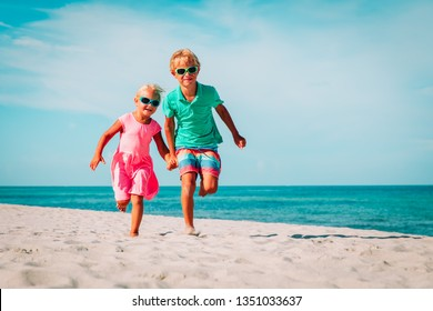 happy little boy and girl running on beach