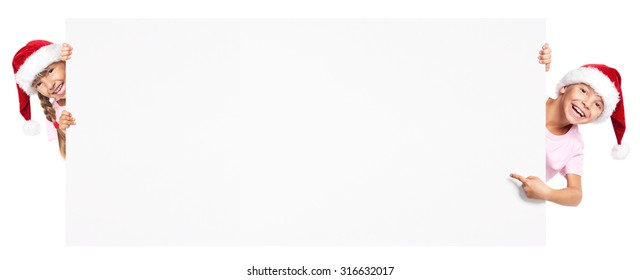 Happy little boy and girl in Santa hat with blank board - isolated on white background