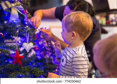 Happy little boy and girl twins decorate Christmas tree