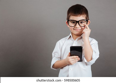 Happy little boy in glasses standing and using mobile phone over grey background