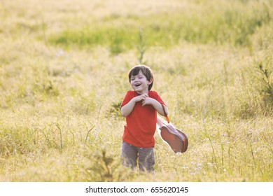 Happy little boy with a guitar on a meadow at sunset. Smiling child with a guitar